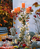 Kerzenhalter dekoriert mit Clematis (Waldrebe, Samenständen), Herbstlaub