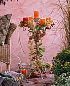 Kerzenhalter dekoriert mit Clematis (Waldrebe), Malus (Zieräpfeln)