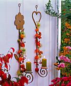 Kerzenhalter an der Wand dekoriert mit Physalis (Lampions), Hagebutten
