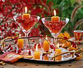 Kerzenhalter aus Gläsern gefüllt mit Hagebutten auf Tablett, Windlichter, Rosa