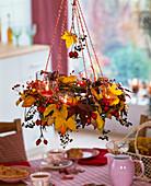 Hängender Kranz mit Herbstlaub von Liquidambar (Amberbaum), Hagebutten, Beeren