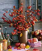 Strauß aus Malus (Zieräpfeln), Stapel mit Geschirr - Handtüchern, Flaschen