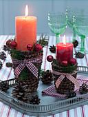 Mit Zapfenschuppen beklebte Tonübertöpfe als Kerzenhalter