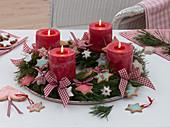 Adventskranz aus Pinus (Kiefer) mit bunten Zimtsternen, roten Kerzen