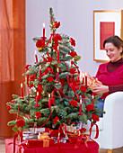 Abies nobilis (Edeltanne) als Weihnachtsbaum geschmückt mit roten Rosa (Rosen