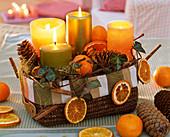 Gesteck mit Citrus (Orangen, Orangenscheiben), Abies (Tannenzapfen), Hedera