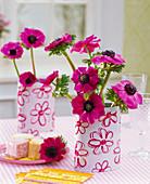 Strauß aus Anemone coronaria (Kronenanemonen) in Dosen mit Blumenmotiven
