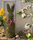 Osterdekoration auf der Terrasse mit Osterhasen aus Stroh, Osternest, Narcissus