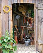 Blick durch offene Türe ins Gerätehaus mit Werkzeug, Schubkarre, Töpfen
