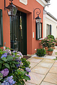 Hauseingang mit Hydrangea (Hortensien), Prunus laurocerasus