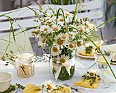 Tischdekoration mit Margeriten und Gräsern