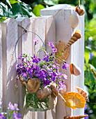 Strauß aus Lobelia (Männertreu) mit Muscheln an Zaun
