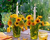 Calendula (Ringelblumen), Foeniculum (Fenchel) in Gläsern mit Kerzen