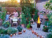LOHAS - Serie: Abendliche Terrasse mit Kerzen und Feuerkorb, Lycopersicon (Tomate), Lathyrus odoratus (Duftwicken), Phaseolus coccineus (Feuerbohnen), Cucurbita (Zucchini), Topfturm und Kasten mit Kräutern, Freunde am Tisch