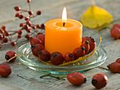 Kerze mit Kranz aus Rosa (Hagebutten) auf Deckel von Einmachglas
