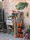 Arbeitsstil: Arbeitstisch mit Tontöpfen, Bambusstangen, Pflanzutensilien