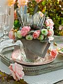 Besteck in Glasvase mit Serviette, Kranz aus Rosa (Rosen)