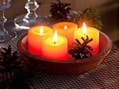 Gelbe Kerzen in getöpferter Schale mit Kiefernzapfen