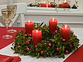 Adventskranz aus Viscum album (Mistel) mit roten Kerzen und Kugeln