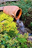 Bachlauf mit liegender Amphore als Quelle, Sedum acre (Mauerpfeffer), Helianthemum (Sonnenröschen)