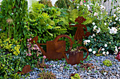 Rostige Garten-Deko im Schotterbeet mit Sempervivum (Hauswurz), Hedera
