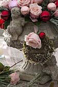 Gesteck aus Rosa (Rosen) und Christbaumkugeln in Steinvase
