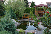 Kleiner Hausgarten mit Teich, Holzbank und Pavillon, Salix 'Hakuro-Nishiki'