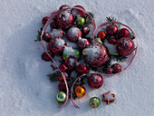 Herz aus Christbaumschmuck in Schnee gelegt