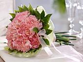 Strauß aus rosa Dianthus (Nelken) mit Laurus (Lorbeer) als Manschette