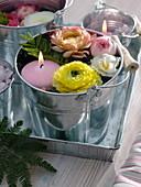 Kleine Becheimer mit Schwimmkerzen und Blüten