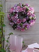 Rosa-weißer Duftkranz an Holzwand