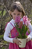Kleines Mädchen mit rosa Hyacinthus (Hyazinthe) im Topf