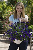 Junge Frau mit frisch gekaufter Viola cornuta (Hornveilchen) im Ampeltopf