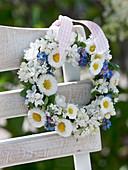 Blau-weißer Frühlingskranz aus Syringa (Flieder), Bellis (Tausendschön