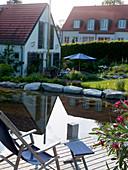 Blick vom Holzdeck im Schwimmteich auf die Terrasse am Haus