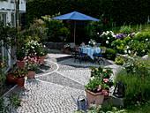 Sternförmig gepflasterte Terrasse mit Kübelpflanzen am Haus