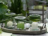Einmachgläser mit Miscanthus (Chinaschilf), Kieselsteinen und Kerzen
