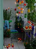 Bunter Sommerbalkon mit Windlichtern, Lichterkette und Lampions