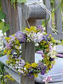 Kleiner Kranz aus Wiesenblumen an Armlehne gehängt