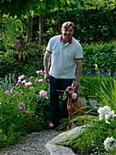 Mann am Beet neben Paeonia (Pfingstrosen), Hund mit Blüte im Maul