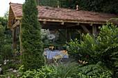 Offenes Gartenhaus als überdachte Terrasse, Thuja 'Smaragd' (Lebensbaum)