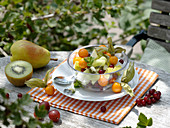 Obstsalat aus Pyrus (Birne), Actinidia chinensis (Kiwi), Physalis