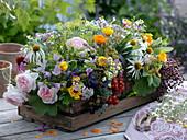Holzkorb mit Gesteck aus frisch geschnitten Blumen, Kräutern und Beeren