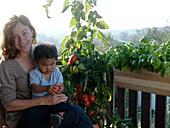 Kleiner Junge mit Tomate auf Mamas Schoß