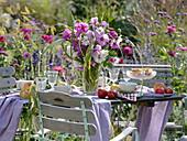 Gedeckter Tisch auf Kiesfläche im Garten