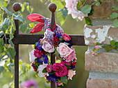 Kranz aus Rosen und Sommerastern am Zaun