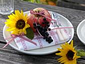 Herbstliche Tellerdekoration mit Sonnenblume und Obst