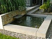 Kleiner architektonischer Teich mit Wasserspiel