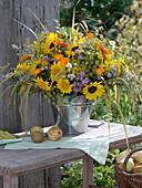 Duftiger Strauß aus Sonnenblumen und Astern in Blechkübel