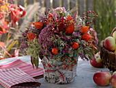 Herbstlicher Strauß mit Fetthenne, Lampionblume und Hagebutten im Birkentopf